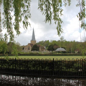 Wrought iron fence in foreground with a view across the Phillips Memorial park towards the Parish Church, taken from under a weeping willow tree on a cloudy day
