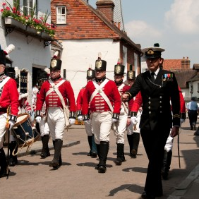 Men marching in old-style red and white military uniforms from the Parish Church along Church Street in sunshine