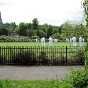 Wrought iron fence in foreground with bowling green behind and bowlers in 'whites' playing a game of bowls with trees in the background