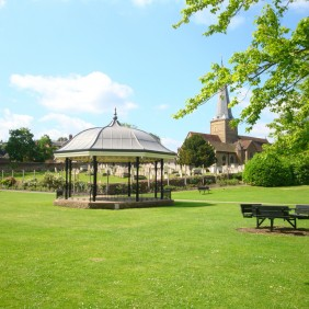 Green lawn leading to Godalming Bandstand with the Parish Church in the background on a sunny day