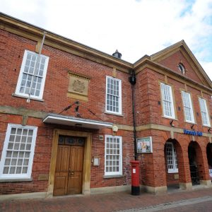 Red brick building showing the frontage of the Town Council offices with bargate stone town crest above the wooden double doors and portico and Georgian windows either side of the door and on the second storey