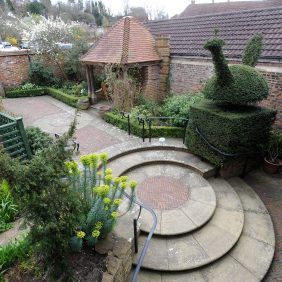 View down into the Godalming Museum's Getrude Jekyll-inspired garden showing brick paving. circular steps, gazebo and topiary.