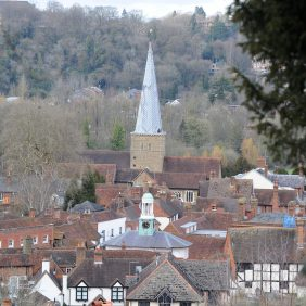View across rooftops of Godalming showing the cupola of The Pepperpot and the spire of the parish church from the vantage point of St Edmund's Steps with wooded hillside on the opposite side of the valley