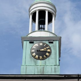 The Cupola of The Pepperpot showing the face of the clock surrounded by verdigris and the bell tower above with a background of blue sky and wispy white clouds
