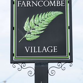 Ornate Farncombe Village sign showing a green fern image on a black background with white lettering and wrought iron curlecues with a background of grey skies