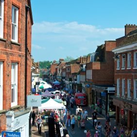 View of Godalming High Street and the stalls of the Easter Festival and crowds of people milling about in the street on a sunny day with blue skies and a few white clouds in the distance